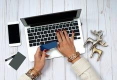 Женщина держа кредитную карточку и используя портативный компьютер Он-лайн принципиальная схема покупкы Стоковые Изображения