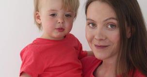 Женщина держа младенца ее оружия акции видеоматериалы