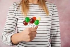 Женщина держа много красочных конфет леденца на палочке на предпосылке цвета стоковое изображение rf