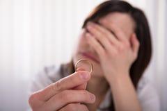 Женщина держа обручальное кольцо стоковое фото