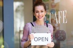 Женщина держа открытое кафе знака внутри стоковые фотографии rf