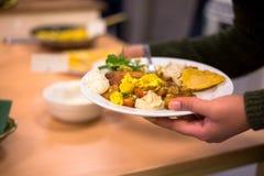 Женщина держа плиту еды vegan стоковая фотография
