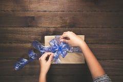 Женщина держа подарки на рождество клала на предпосылку деревянного стола приветствие рождества карточки веселое открытый космос Стоковое Изображение