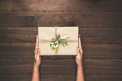 Женщина держа подарки на рождество клала на предпосылку деревянного стола приветствие рождества карточки веселое открытый космос Стоковое фото RF