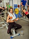 Женщина держа разминку гантели на спортзале Стоковые Изображения