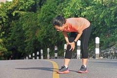 Женщина держа раненое колено пока бегущ в парке Стоковое фото RF