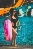 Женщина держа розовое раздувное кольцо около бассейна с скольжениями стоковая фотография rf