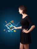 Женщина держа самомоднейшую таблетку с цветастыми диаграммами и диаграммами Стоковые Фото