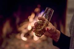 Женщина держа стекло шампанского перед камином Стоковые Фотографии RF
