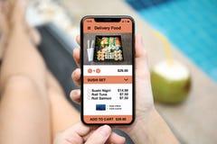 Женщина держа телефон с едой суш поставки app на экране Стоковые Изображения