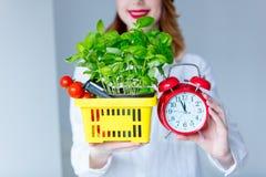 Женщина держа травы базилика и красные томаты в условный расчетный набор представительных потребительских товаров Стоковые Фотографии RF