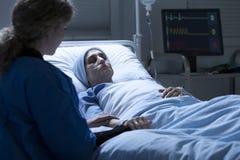 Женщина держа умирая руку ` s матери стоковое фото rf