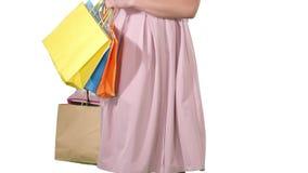 Женщина держа хозяйственные сумки в ее руках и делая поворот на белой предпосылке видеоматериал