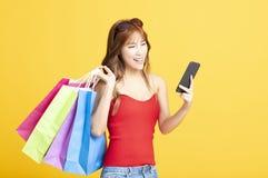 женщина держа хозяйственные сумки и умный телефон стоковое фото rf