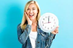 Женщина держа часы показывая почти 12 Стоковая Фотография
