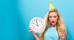 Женщина держа часы показывая почти 12 Стоковые Фото