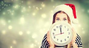 Женщина держа часы показывая почти 12 Стоковая Фотография RF