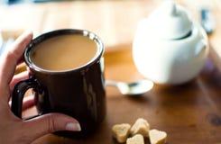 Женщина держа чашку горячего кофе в руках с сердцем сформировала кубы сахара на темной деревянной таблице стоковые фото