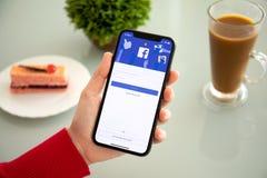 Женщина держа iPhone x с социальным обслуживанием Facebook сети стоковая фотография