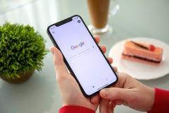 Женщина держа iPhone x с социальным обслуживанием Google сети стоковая фотография rf
