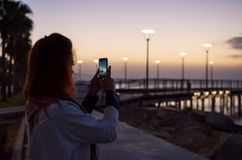 Женщина держа smartphone фотографируя снаружи во время восхода солнца пристань Кипра limassol стоковые фотографии rf