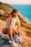 Женщина держит бутылку воды в природе на теплом заходе солнца Привлекательный hiker девушки в горах Стоковые Изображения