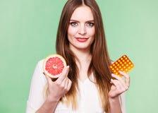 Женщина держит Витамин C пакета грейпфрута и волдыря пилюлек Стоковое Изображение