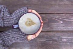Женщина держит горячий latte чашки кофе, капучино с сливк молока и валентинку сердца, влюбленность, грея ее руки на деревянном ко Стоковая Фотография