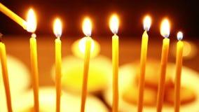 Женщина держит горящую свечу в ее руке с которой она освещает свечи в подсвечнике Хануки женщина освещает свечи от th сток-видео