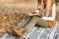 Женщина держит книгу и чашку кофе на ногах и чтение на ретро одеяле в парке стоковое фото