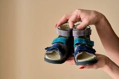 Женщина держит конец-вверх сандалии протезного ботинка особенных детей сделанный из неподдельной кожи стоковые изображения rf