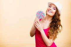 Женщина держит красочную конфету леденца на палочке в руке стоковое фото