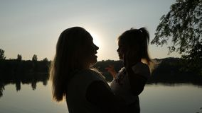 Женщина держит маленькую девочку в ее оружиях и целует ее озером на времени захода солнца видеоматериал