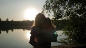 Женщина держит маленькую девочку в ее оружиях и целует ее озером на времени захода солнца сток-видео