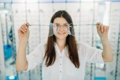 Женщина держит огромные декоративные стекла, оптический магазин стоковое изображение