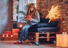 Женщина держит подарок рождества в живущей комнате с интерьером просторной квартиры стоковое фото rf