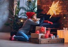 Женщина держит подарок рождества в живущей комнате с interi просторной квартиры Стоковое Изображение