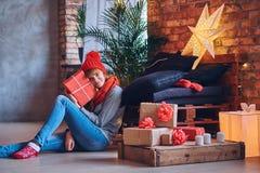 Женщина держит подарок рождества в живущей комнате с interi просторной квартиры Стоковые Изображения
