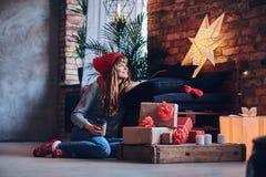 Женщина держит подарок рождества в живущей комнате с interi просторной квартиры Стоковые Фотографии RF