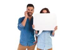 Женщина держит пузырь речи пока человек говорит на телефоне Стоковая Фотография RF
