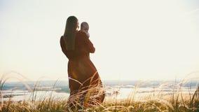 Женщина держит ребенка в ее оружиях Против фона захода солнца видеоматериал