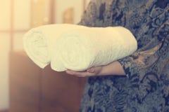 Женщина держит свернутое полотенце стоковые изображения rf