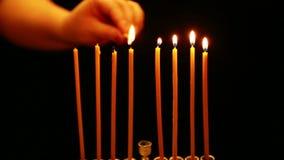 Женщина держит свечу в ее руке и освещает свечи в подсвечнике Хануки Движение камеры справа налево сток-видео