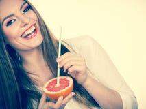 Женщина держит сок грейпфрута выпивая от плода стоковая фотография