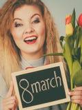 Женщина держит тюльпаны, доску с текстом 8-ое марта стоковые фото