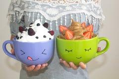 Женщина держит 2 больших кружки с покрашенными сторонами, с взбитыми сливк и ягодами Мусс шоколада с клубниками и ванилью стоковые фотографии rf