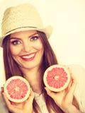 Женщина держит 2 halfs цитрусовых фруктов грейпфрута в руках Стоковое Изображение