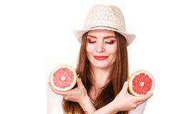 Женщина держит 2 halfs цитрусовых фруктов грейпфрута в руках Стоковое фото RF