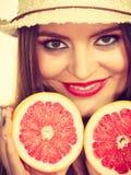 Женщина держит 2 halfs цитрусовых фруктов грейпфрута в руках Стоковые Изображения