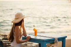 Женщина детенышей подходящая в посадочных местах обмундирования лета на деревянном голубом бушеле стула стоковые изображения